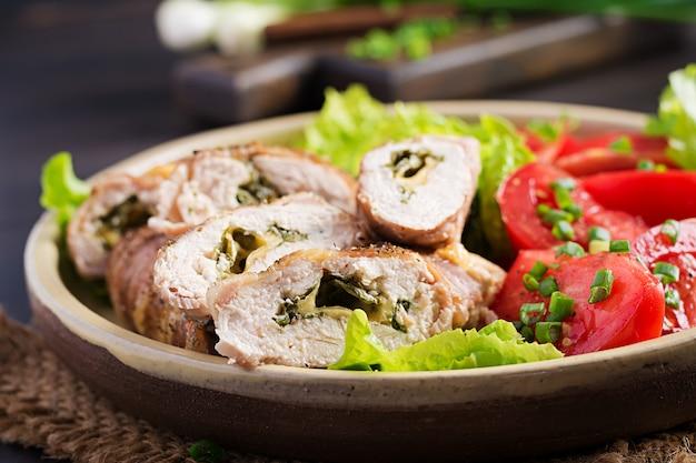 Leckere hähnchenröllchen gefüllt mit käse und spinat in speckstreifen.