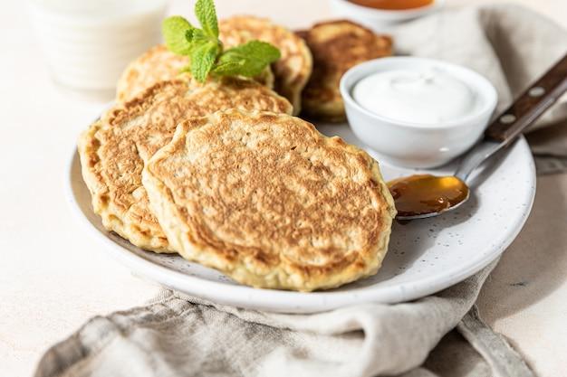 Leckere haferflocken-pfannkuchen serviert mit marmelade und naturjoghurt auf keramikplatte