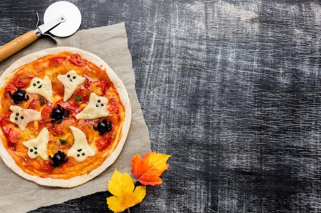 Leckere halloween-pizza mit herbstlaub