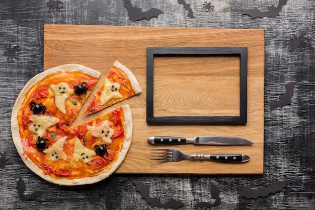 Leckere halloween-pizzascheiben mit besteck und rahmen