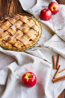 Leckere hausgemachte apfelkuchenzusammensetzung auf leinentuch. layout oder stillleben mit hausgemachter charlotte in form zum kochen auf tisch mit leichter tischdecke auf küche zu hause bedeckt.