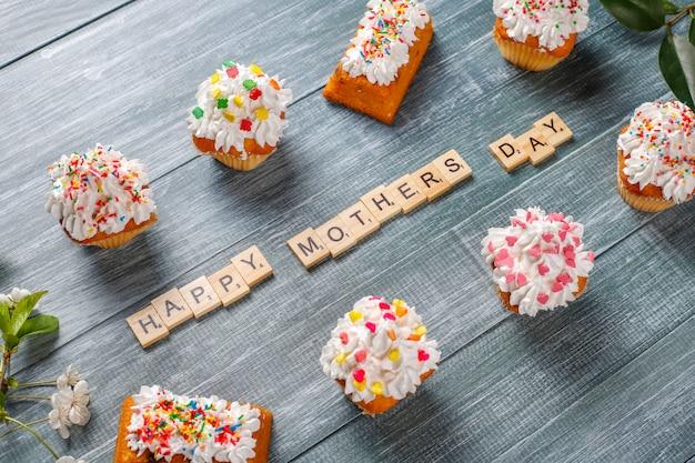 Leckere hausgemachte cupcakes mit verschiedenen streuseln und glücklichen muttertagswörtern