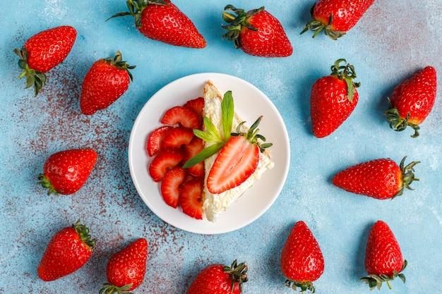 Leckere hausgemachte erdbeerkuchenscheiben mit sahne und frischen erdbeeren, draufsicht