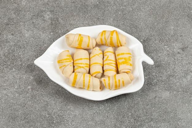 Leckere hausgemachte kekse auf blattförmigem teller