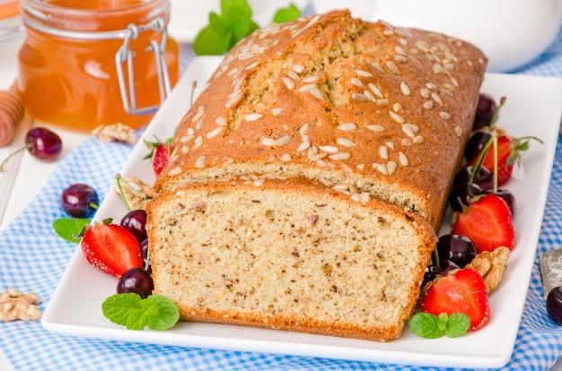 Leckere hausgemachte kuchen mit walnüssen und sonnenblumenkernen. serviert mit frischen beeren und honig.