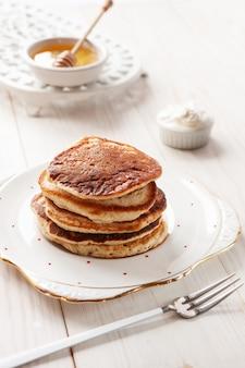Leckere hausgemachte pfannkuchen mit sauerrahm und honig