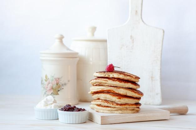 Leckere hausgemachte pfannkuchen mit sauerrahm und marmelade.