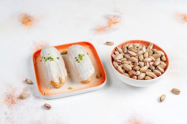 Leckere hausgemachte pistazien-eclairs mit weißer schokolade.