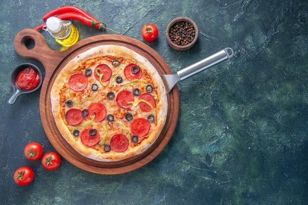Leckere hausgemachte pizza auf holzbrett ölflasche tomaten pfeffer auf der rechten seite auf dunkler oberfläche
