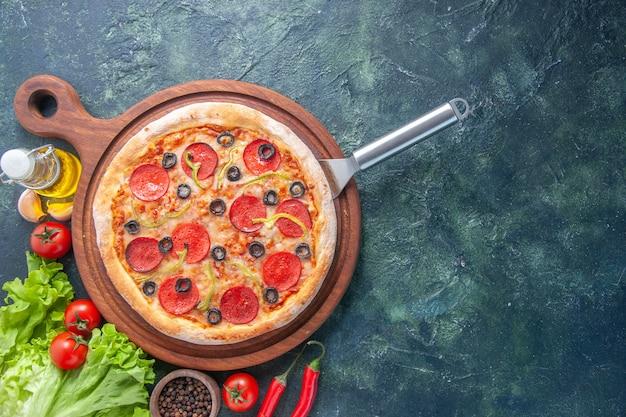 Leckere hausgemachte pizza auf holzbrett ölflasche tomaten pfeffer grünes bündel auf der rechten seite auf dunkler oberfläche