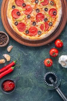 Leckere hausgemachte pizza auf holzbrett und knoblauch-tomaten-ketchup auf isolierter dunkler oberfläche