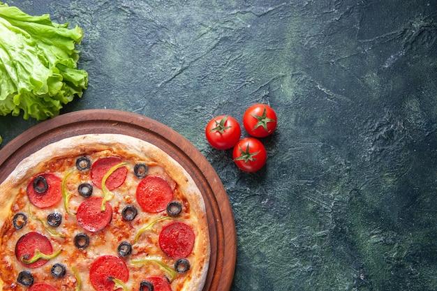 Leckere hausgemachte pizza auf holzschneidebrett tomaten ketchup grünes bündel auf dunkler oberfläche