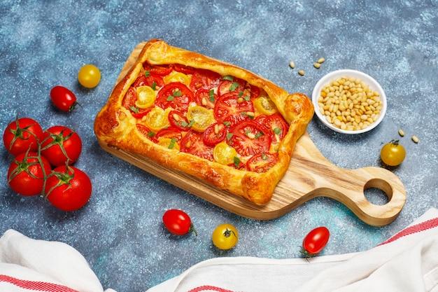 Leckere hausgemachte rustikale offene torte, galette mit verschiedenen tomaten und pinienkernen