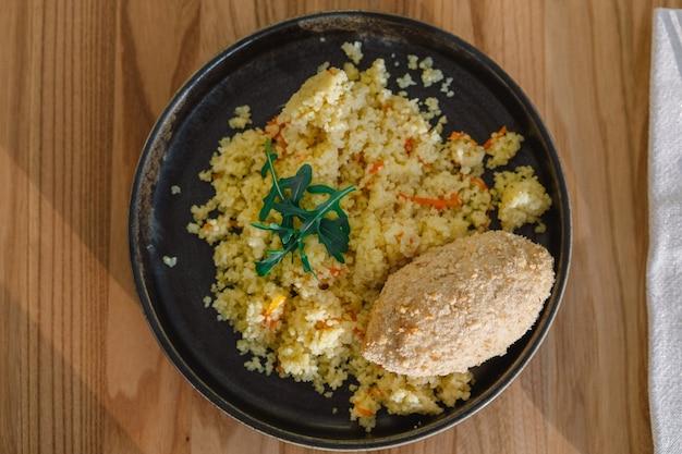 Leckere hausgemachte schnitzel, couscous mit gemüse und rucola.