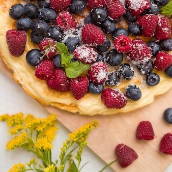 Leckere hausgemachte torte mit bio-himbeeren und blaubeeren und sommerblumen auf holzbrett