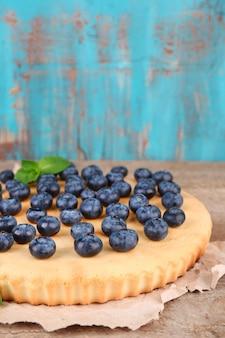 Leckere hausgemachte torte mit blaubeeren auf holztisch