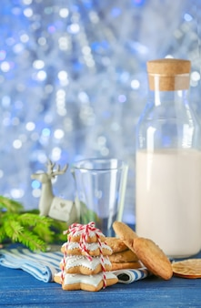 Leckere hausgemachte weihnachtskekse und flasche mit milch auf dem tisch