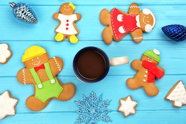 Leckere hausgemachte weihnachtsplätzchen und eine tasse kaffee auf farbholztisch wooden