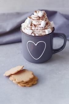 Leckere heiße schokolade mit schlagsahne und kekse auf einem grauen stein hintergrund