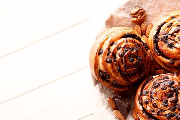 Leckere heiße zimtschnecken und schokolade auf weißem holzhintergrund. süße zimtschnecken frisch hausgemacht. platz für text. ansicht von oben.