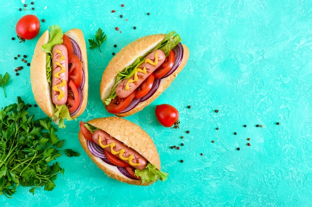 Leckere hot dogs. gegrillte wurst mit tomaten, roten zwiebeln, salat, senf in einem knusprigen laib. straßenessen. fast food. die draufsicht