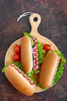 Leckere hot dogs mit wurstgrill, ketchup, senf, salat, tomaten auf einem holztablett. draufsicht, flach liegen.