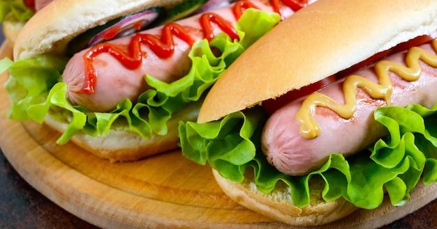 Leckere hot dogs mit wurstgrill, ketchup, senf, salat, tomaten auf einem holztablett. nahansicht