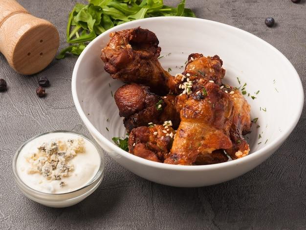 Leckere hühnerflügel mit käsesauce in einer weißen schüssel auf grauem hintergrund