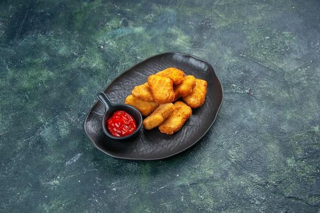 Leckere hühnernuggets und ketchup in schwarzer platte auf dunkler oberfläche
