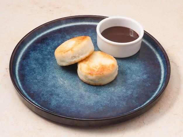 Leckere hüttenkäsepfannkuchen mit einem konzept-frühstück mit schokoladenüberzug