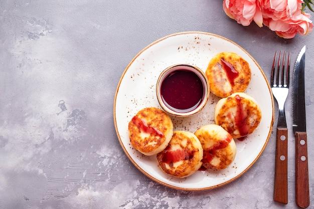 Leckere hüttenkäsepfannkuchen mit roter fruchtsauce.