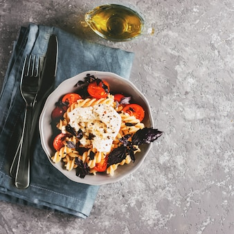 Leckere italienische fusilli-nudeln mit kirsch-, mozarella- oder buratta-käse und frischem basilikum. gericht mit nudeln auf grauem betonhintergrund. draufsicht.