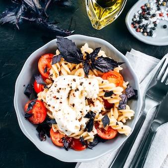 Leckere italienische fusilli-nudeln mit kirsch-, mozarella- oder buratta-käse und frischem basilikum. gericht mit nudeln auf schwarzem betonhintergrund. draufsicht.