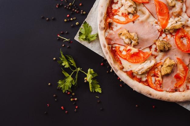 Leckere italienische pizza und kochende zutaten tomaten, kräuter, käse auf schwarz lokalisiert auf hintergrund