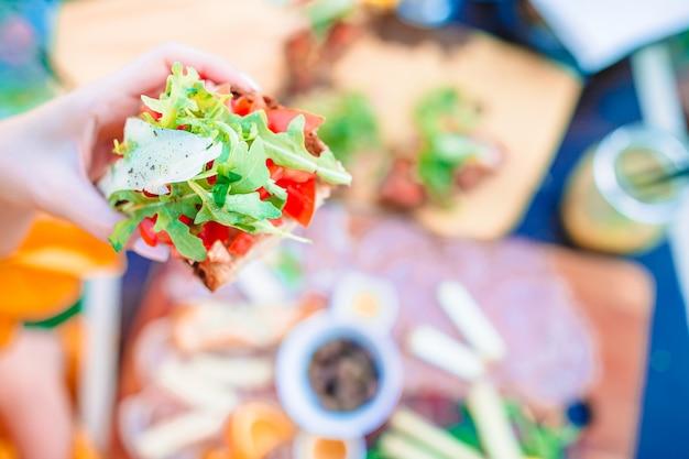Leckere italienische zwischenmahlzeit. frische bruschettes, käse und fleisch auf dem brett im café mit ansicht in manarola
