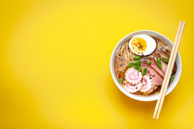 Leckere japanische nudelsuppe ramen in weißer keramikschale, fleischbrühe, geschnittenes schweinefleisch, narutomaki, ei mit eigelb auf pastellgelbem hintergrund. traditionelles japanisches gericht, draufsicht, nahaufnahme, platz für text