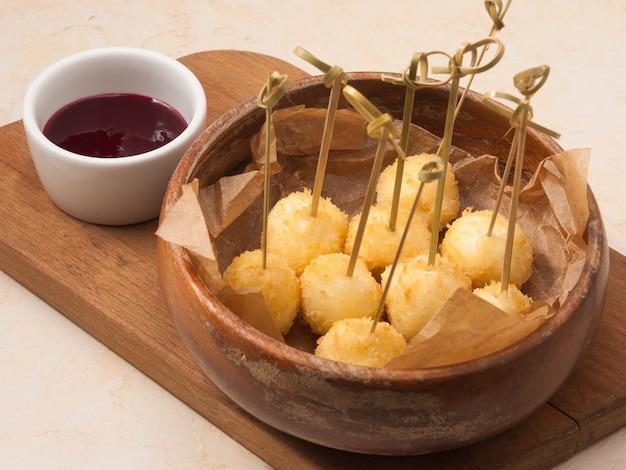 Leckere käsebällchen mit beerensauce im restaurant