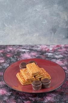 Leckere kakaokekse und knusprige cracker auf rotem teller.