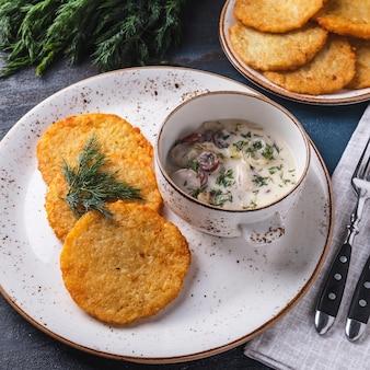 Leckere kartoffelpuffer mit würstchen in soße. machanka. traditionelles belarussisches gericht.