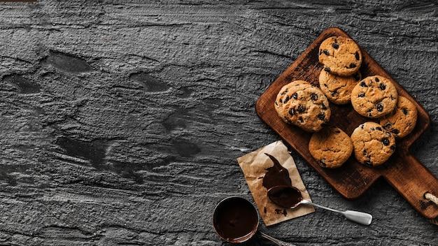 Leckere kekse auf holzbrett mit schokolade