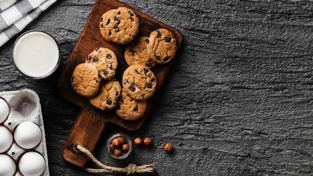 Leckere kekse auf holzbrett und glas milch