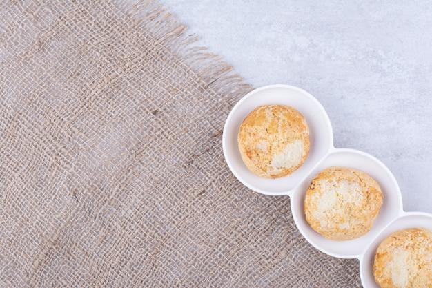 Leckere kekse in weißen schalen mit sackleinen