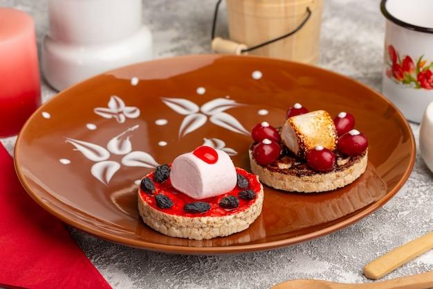 Leckere kekse mit hartriegeln in brauner platte auf grau