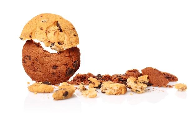 Leckere kekse mit schokoladenstückchen und krümel auf weiß