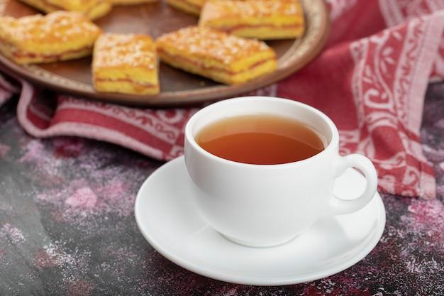 Leckere kekse mit sesam und tasse tee auf lila oberfläche.