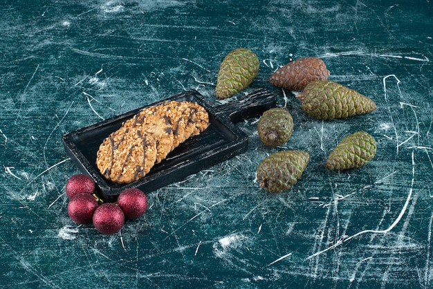 Leckere kekse mit tannenzapfen und weihnachtskugeln. foto in hoher qualität