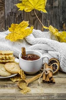 Leckere kekse und eine tasse heißen tee mit einer zimtstange und einem löffel braunem zucker auf holz mit gelbem herbstlaub,