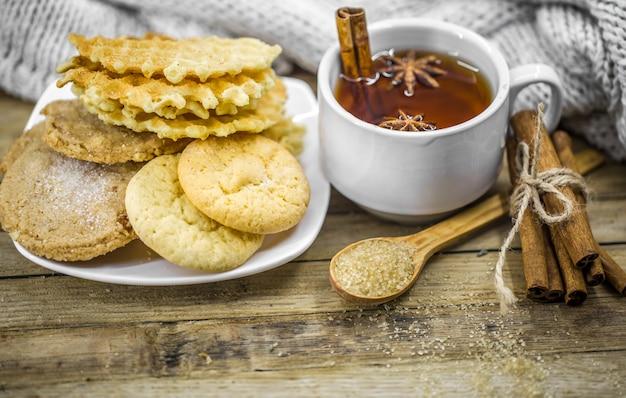 Leckere kekse und eine tasse heißen tee mit einer zimtstange und einem löffel braunem zucker auf holz