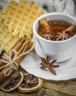 Leckere kekse und eine tasse heißen tee mit einer zimtstange