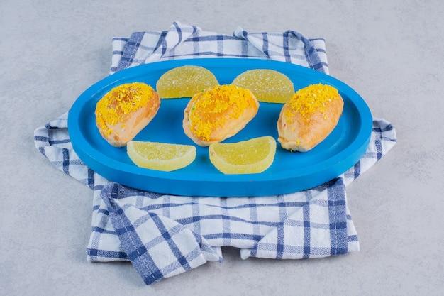 Leckere kekse und marmeladen auf blauem teller.